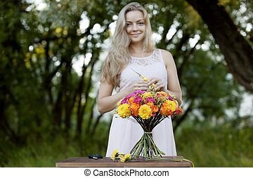 Young beautiful woman florist. The girl in the Park draws a...