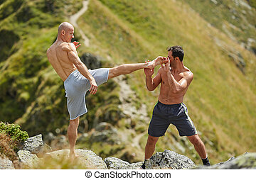 Kickbox fighters sparring in the mountains - Kickboxers or...