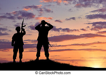 Silhouette of two soldiers on exploration at sunset