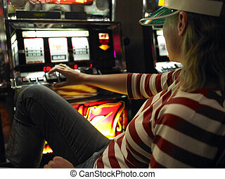 Young Woman Sitting and Playing Slot Machine - Young woman...