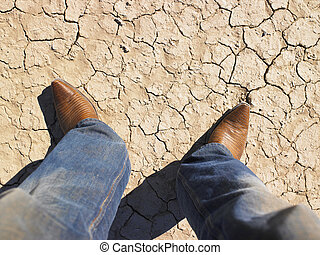 Person in Jeans and Cowboy Boots Standing on Cracked Dirt -...