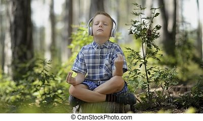 Little Boy Meditating In The Forest