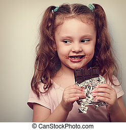 Curious cute kid girl eating dark chocolate and looking fun...