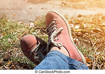 Feet in red sneakers and jeans outdoors - Legs crossed in...