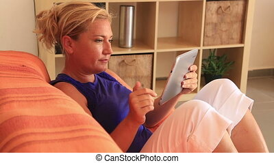 woman using ipad - Woman sitting on sofa and using digital...