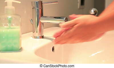 Woman washing hand with soap under running water