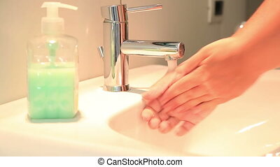 Woman washing hand with soap