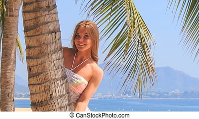 blonde girl in lace closeup looks out of palm touches hair -...
