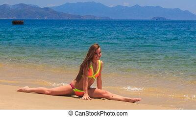 blond girl in bikini sits in split on wet sea sand waves...