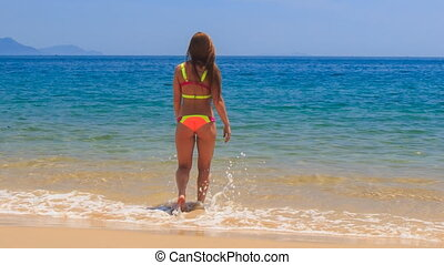 blond slim girl in bikini backside view steps into sea water...
