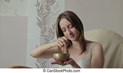 Young beautiful lady relaxing with nepal singing bowl, HD