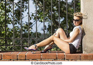 woman sitting on a brick fence - Young attractive blond...