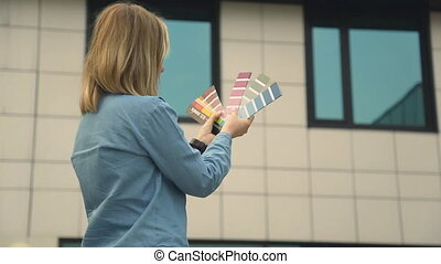 Female interior designer holding color guide - White woman...