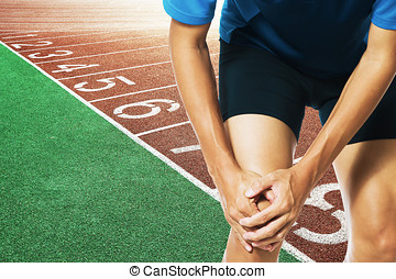 Male athlete runner touching foot in pain due to sprained...