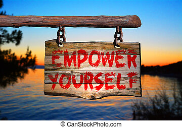 Empower yourself sign on old wood with a blurred sunset on...