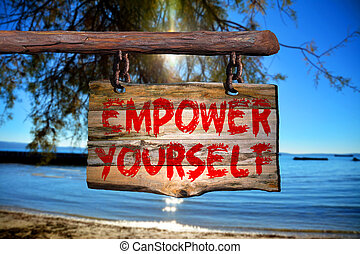 Empower yourself sign on old wood with a blurred beach on...