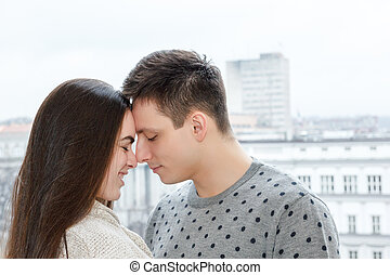 Loving couple touching noses outdoors with city view -...