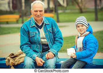 Grandfather and grandson eating fries and indulge