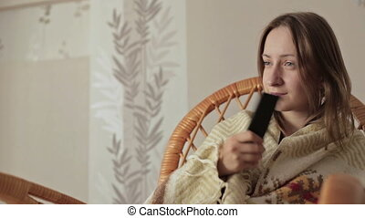 Young woman covered with blanket holding remote control and watching tv at home