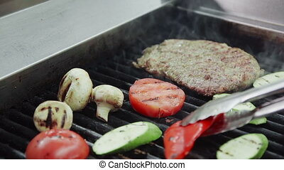 Professional chef cooking meat and vegetables on barbecue...