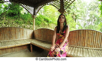 Girl in wooden gazebo - Camera on steadicam flies in wooden...