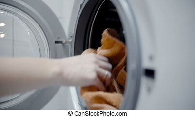 woman loading the laundry in the washing machine slow motion