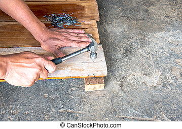 Carpenter nailing the teak wood board by hammer in Thailand to make furniture from old wood