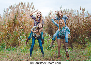 Four girlfriends playing horses and having fun in autumn countryside