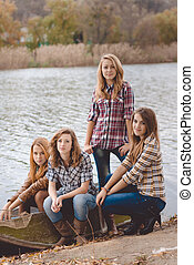 Four pretty girls in jeans smiling beside river on autumn