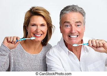 Happy elderly couple with toothbrush.