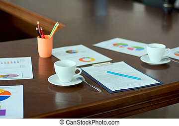 Conference hall. Paper documents, graphs. Cups for coffee...