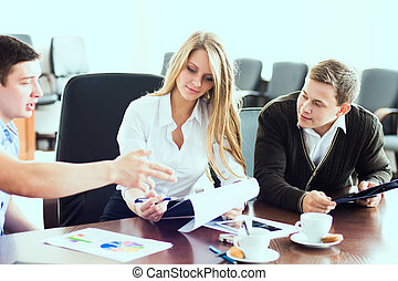 Young beautiful business woman with business partners, men...