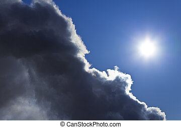 The Sun and Blue Sky Emerges From Behind a Storm Cloud -...