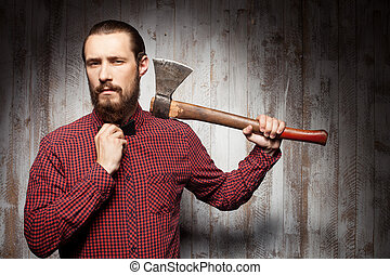 Handsome young bearded man is using axe - Attractive...