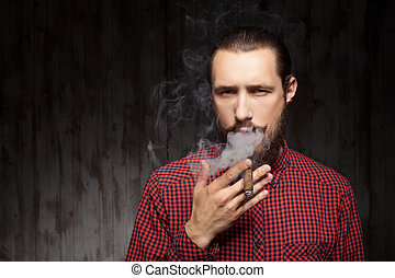 Attractive young bearded man is relaxing with cigarette -...