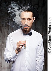 Handsome bearded hipster guy with cap and cigarette -...