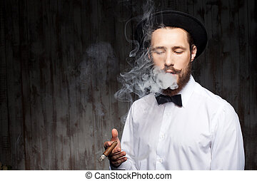 Attractive young bearded guy with hat and cigarette -...