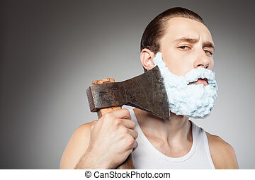 Attractive young bearded guy shaves with hatchet - Cheerful...
