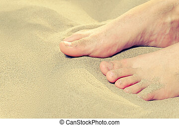 Macro of teen girl feet on sand and space for text