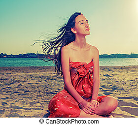 Long haired brunette meditate on sandy beach with flattering...