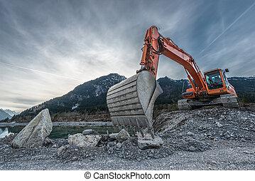 big orange digger on gravel heap with big shovel