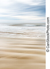 Sand and Water in Motion - A soft focus seascape with...