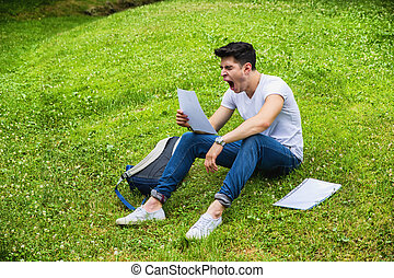Young Bored, Tired Male Student Studying in City Park -...