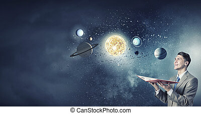 Space exploration - Young businessman with book and planets...
