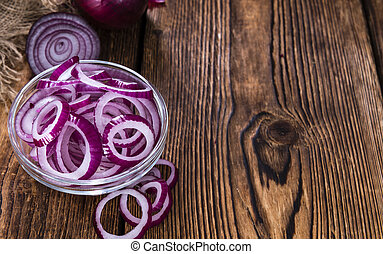 Fresh cutted Red Onion rings close-up shot on an old wooden...