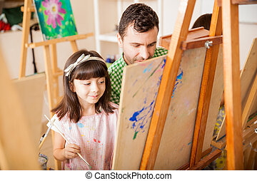 Teacher helping student with her painting