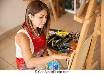 Young woman working on a painting