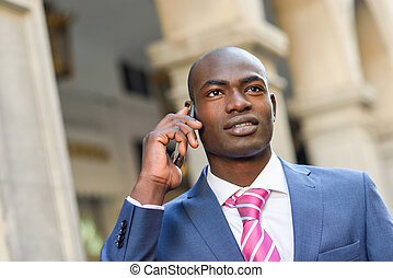 Black businessman talking with his smart phone in urban...