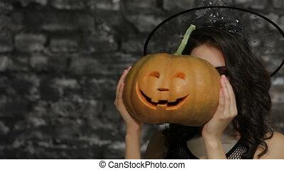 A woman-sorceress covers her face pumpkin