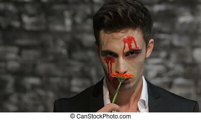 Male vampire smelling a flower and gives it Rack Focus on...